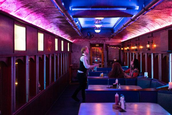 """The New York Times - From the series """"52 Places to Visit in 2019""""March 19th, 2019 """"Another place I loved was A.M. Booth's Lumberyard, a deceptively gigantic space that includes multiple bars, outdoor patios, music stages and a restored train car from the 1920s that you can have dinner in.""""- Sebastian Modak/The New York Times"""