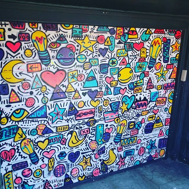 "amazing garage-door graffiti mural! sort of in the style of Keith Haring but more multilayered, and with messages hidden in plain sight the longer you look -- including, pictured here: *binary code *""omg it's DNA!' *food pyramid *'it's ok'"