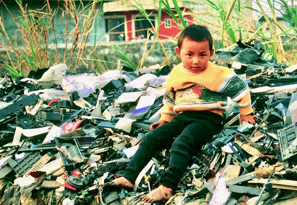 Boy in Guiyu, China, atop a pile of electronic waste. Creative Commons, Basil Action Network, 2017.