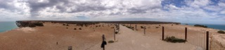 Panoramic view from on top the cliffs. The desert is alive with low lying vegetation.