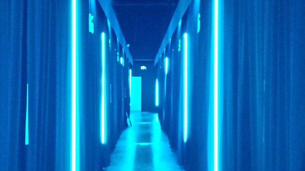 A corridor of virtual reality pods.