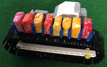 The rescue packages on a conveyor belt, squeezed in between multiple 3M friction pegs. (Image taken from Robocup Junior)