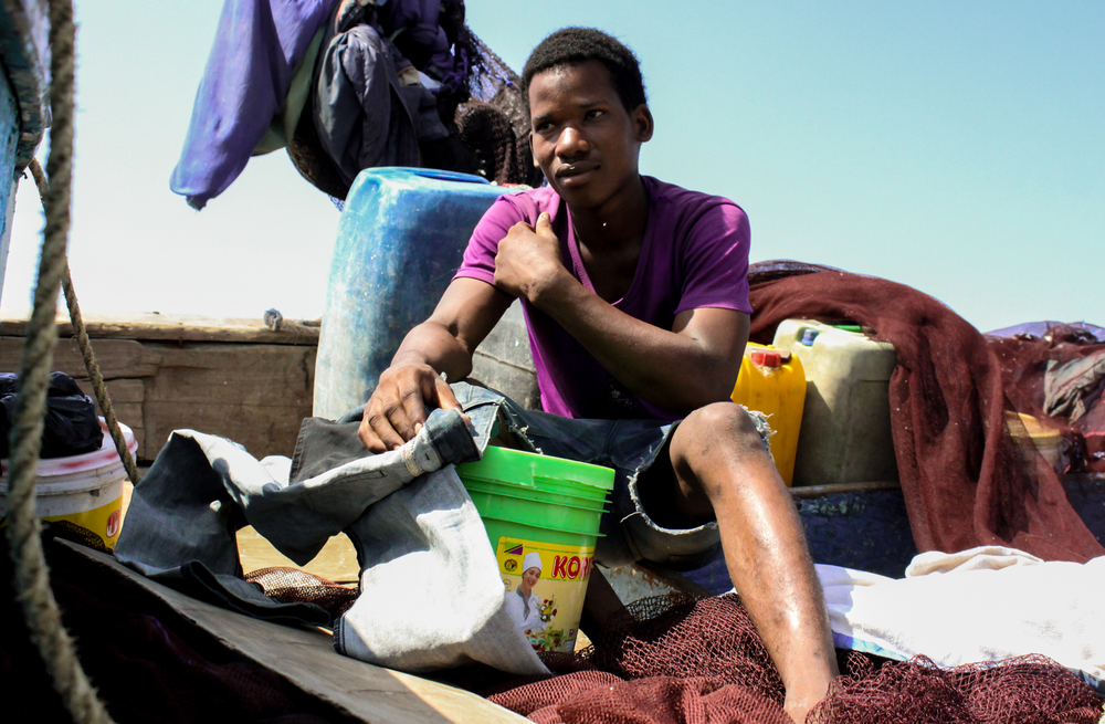 A young fisherman repairs his jeans while waiting for the tide to return in Bagamoyo, Tanzania