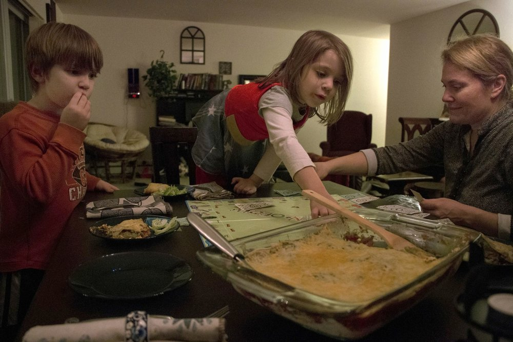 "Shiloh (center) and her brother Liam (left) play monopoly while eating dinner in their new apartment. Kirianne has a joint custody with her former husband Marcus and takes care of her two children for at least four days a week. Kirianne said that although she no longer has a relationship with her husband, Marcus is still their father.  ""It's been a relief to no longer live under the same roof [as Marcus]. He had depression and anxiety issues that turned into anger issues. The kids and I needed to leave,"" she said. ""It got to the point where I didn't want to become a statistic."""