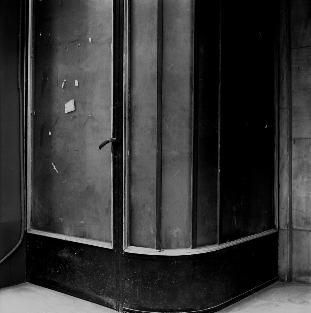 Becky Beasley, Left Door, 2004/2005. Gloss fibre-based gelatin silver print, Archival linen tape, metal eylets.120 x 120 cm. Courtesy Laura Bartlett Gallery, London.