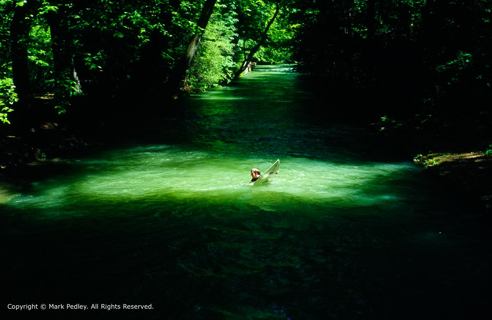 Surfer in the River Eisbach near the English Garden, Munich, Germany.