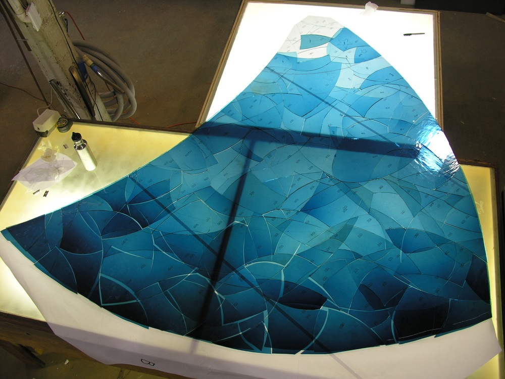 This is the blue glass now laid out correctly, to make sure that all the pieces are there and that we aren't missing any sections. The glass is being prepared to be etched.