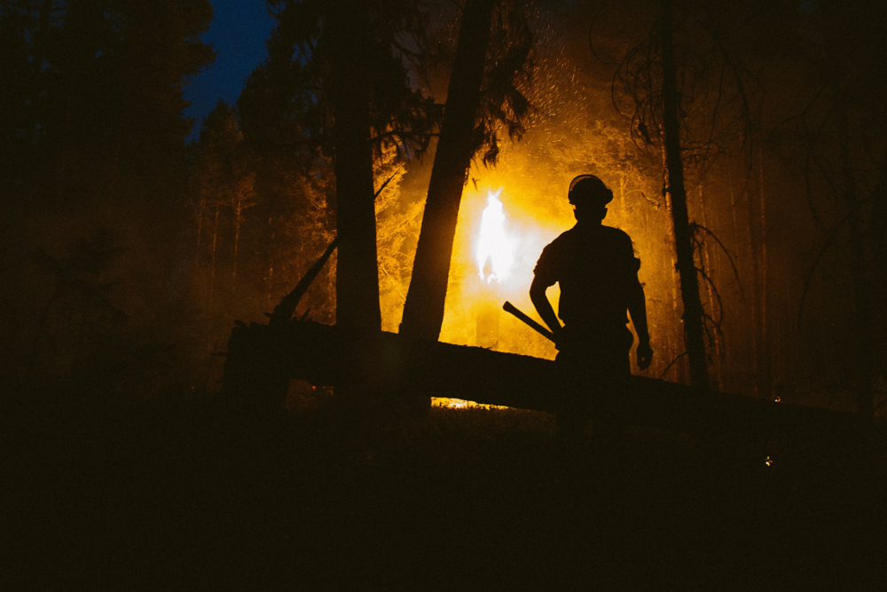 A wildfire firefighter keeps an eye on a fire line near Williams Lake, B.C. Photo: Will Eason