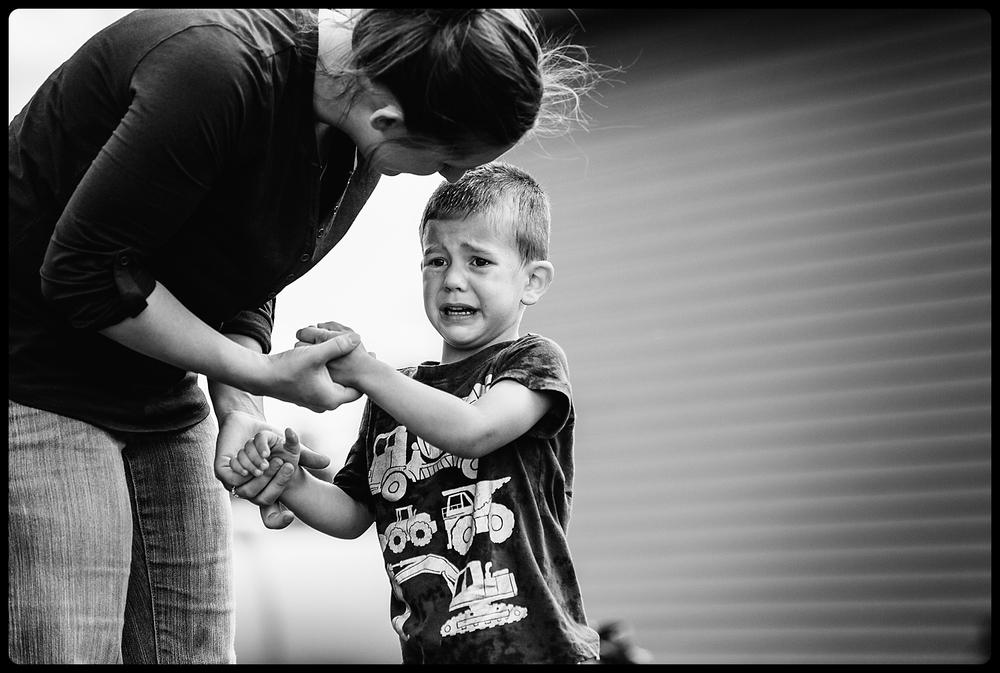 Boy upset as mom comforts him.
