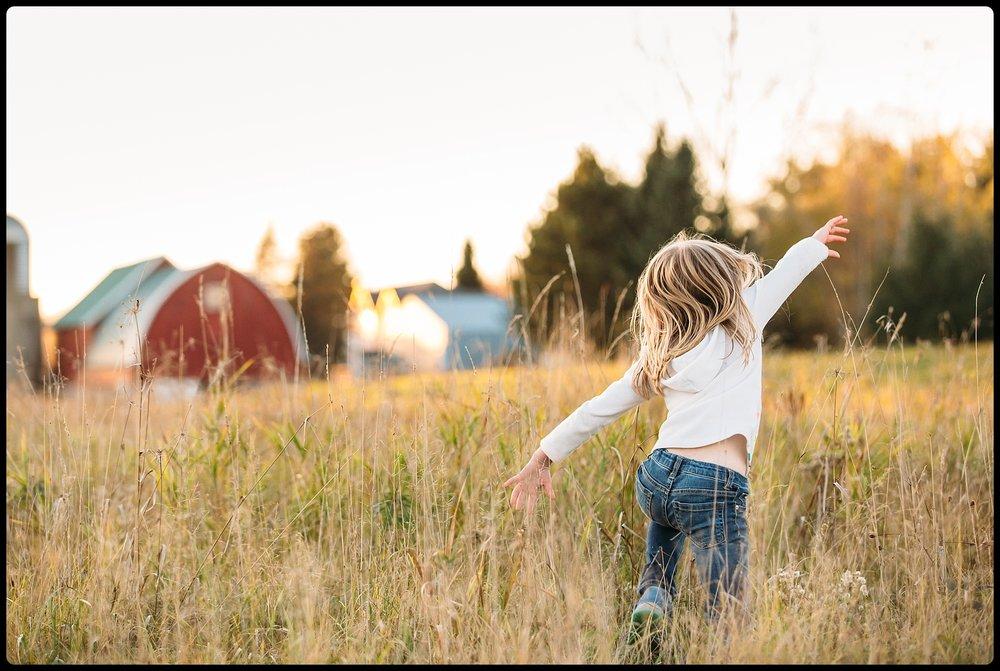 Girl playing in a field near a barn.