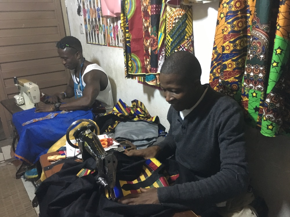 KOMBA & ASSISTANT PROUDLY WORKING IN HIS OWN SHOP