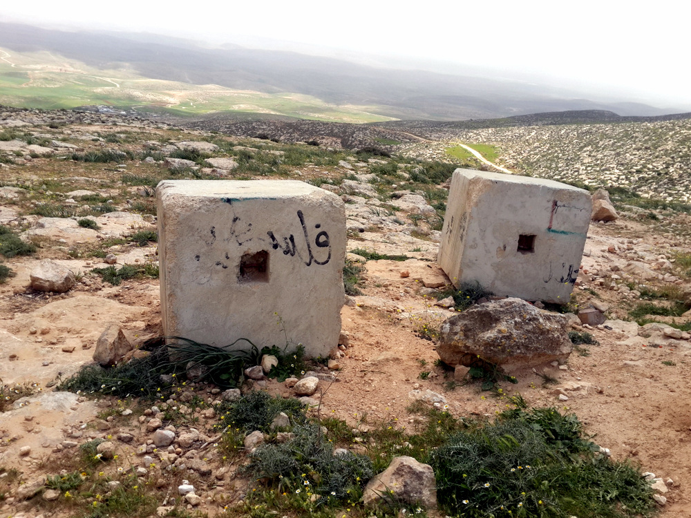 Concrete blocks placed by the military on the western access road to the Masafer Yatta area. The houses of Khirbet Jenbah are seen at the bottom of the valley.  Photo by Osnat Skoblinski for B'Tselem.