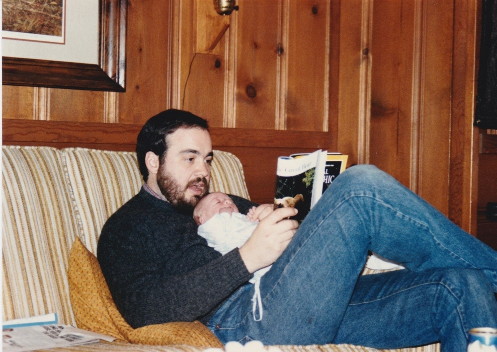 (Pictured Above) Rachel as an infant reading National Geographic with her father. The curiosity and love for language and story started early!