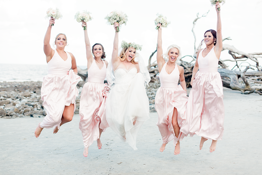 Bride and bridesmaids jumping in Driftwood beach wedding