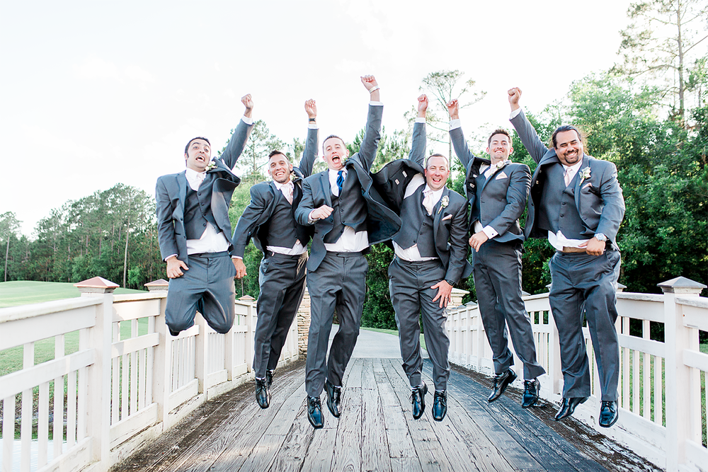 groom and groomsmen jumping on the bridge
