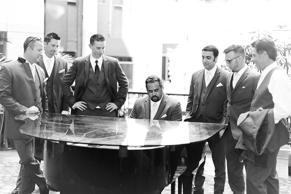 Groom and groomsmen playing a piano