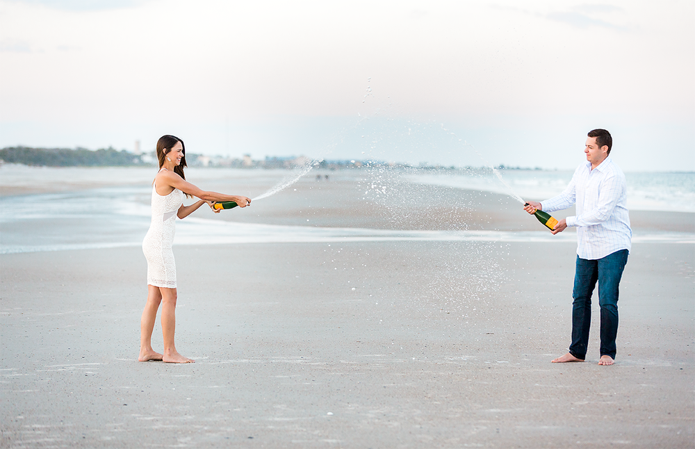 spraying champagne during sunset engagement session at the beach