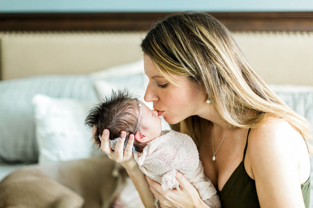 mommy kissing her baby girl during newborn session