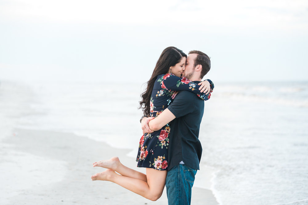 couple kissing at the beach during engagement pictures