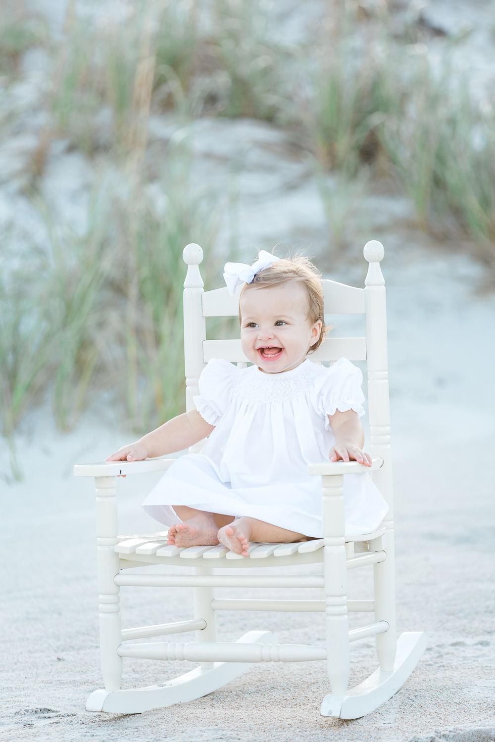 baby girl in a rocking chair at the beach