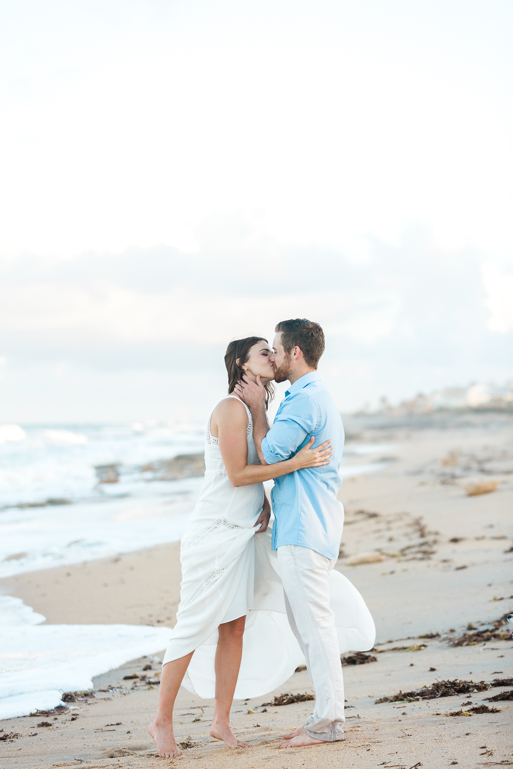 engaged couple kissing at the beach