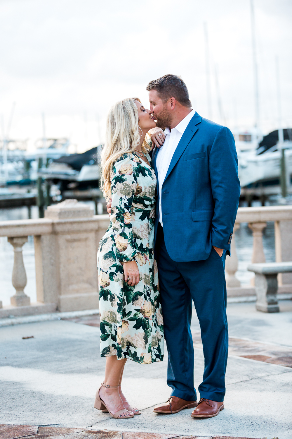 engaged couple kissing at the yacht club