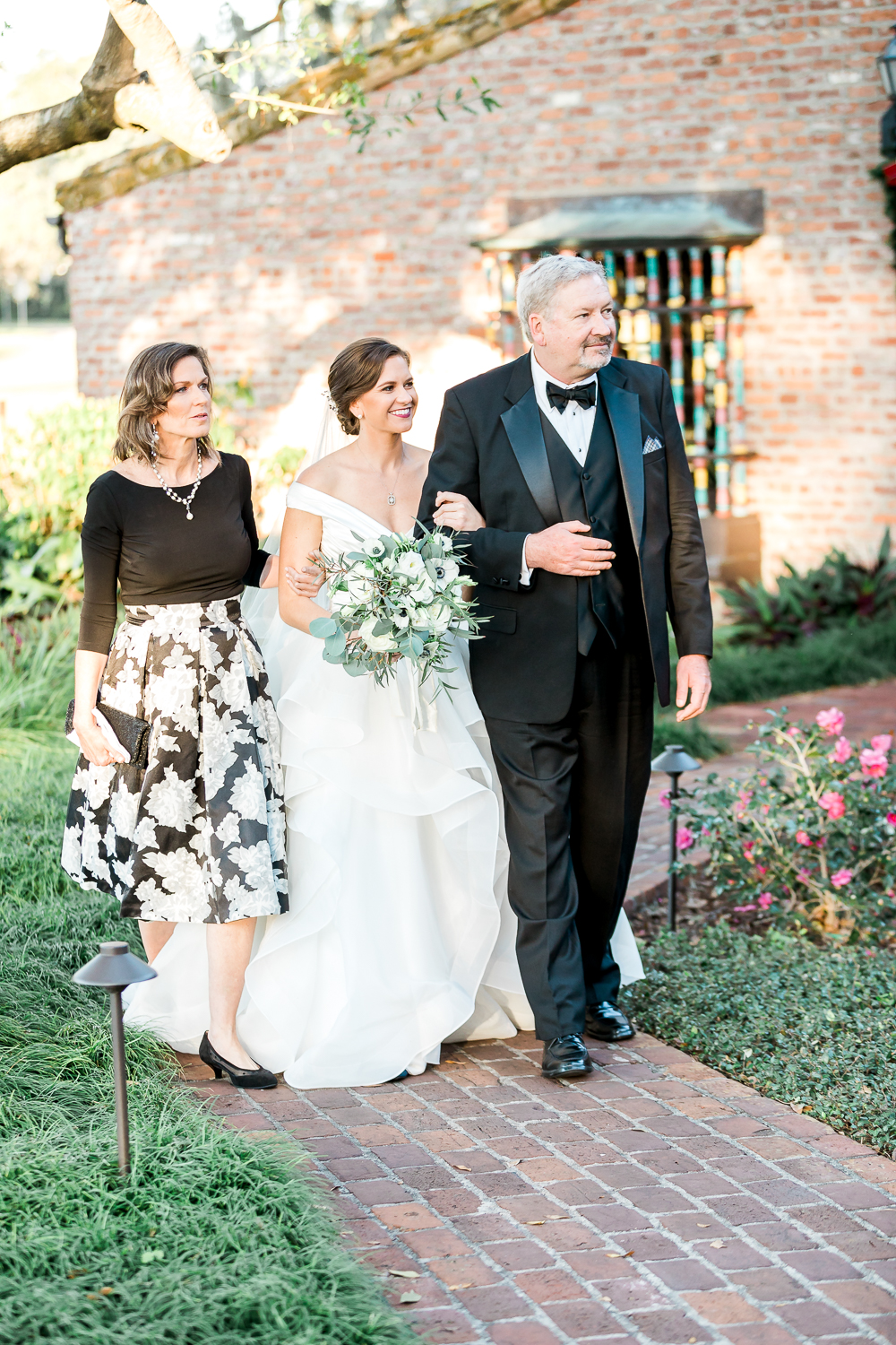 bride walking down the isle with her parents