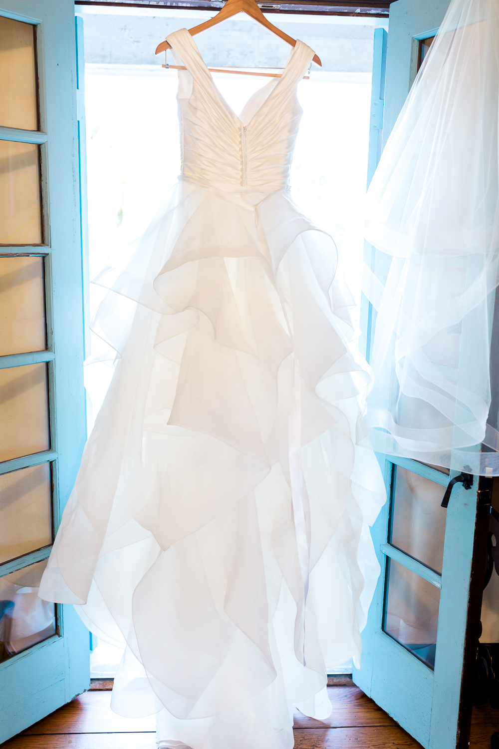 Maggie Sottero wedding dress hanging on the door