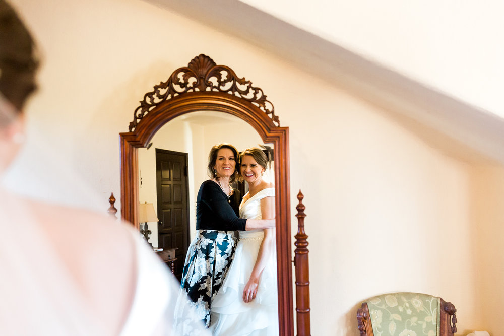 bride and bride's mom looking themselves in the mirror