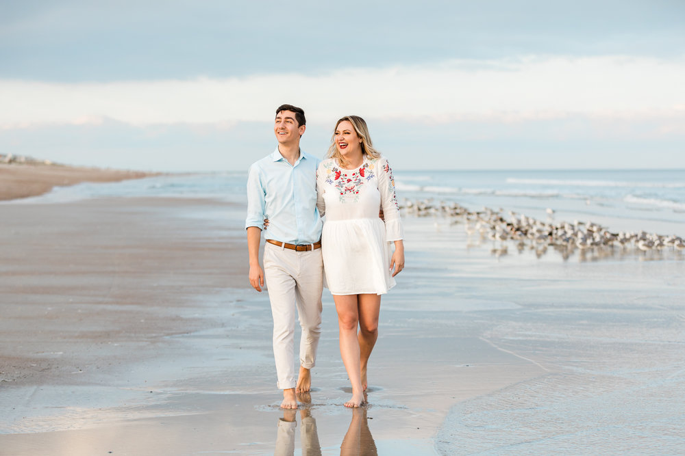 engagemet couple walking at the beach