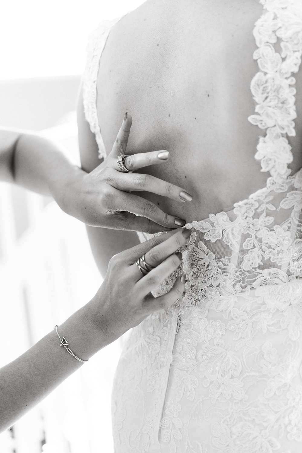 mom helping bride to get dressed