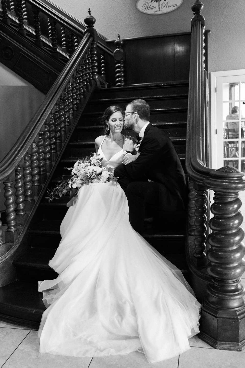 bride and groom sitting on the stairs in the white room