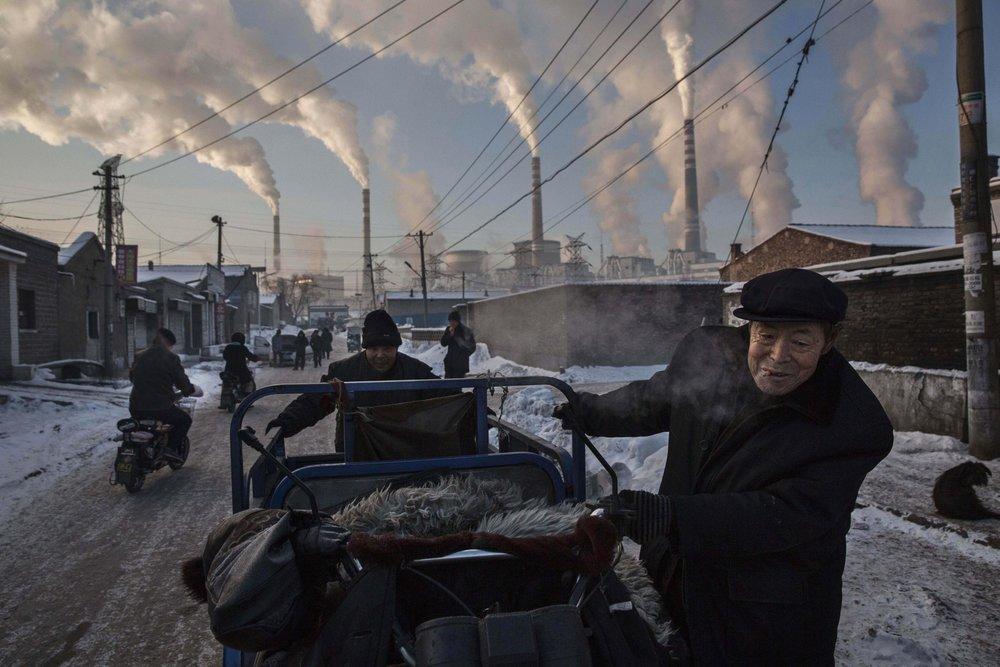 """""""China's Coal Addiction""""  Kevin Frayer - China  Primer lugar en categoría individual  Descripción: Impresionante humo sale de tubos de de una planta industrial de carbón y energía mientras unos hombres empujan un mini transporte. Este lugar esta situada en Shanxi, en el noroeste de China y es la región líder en producción de carbón excediendo el número a 300 toneladas anuales de producto. Se supone que gracias a estas industrias, la contaminación estima un 17% de todas las muertes de china"""