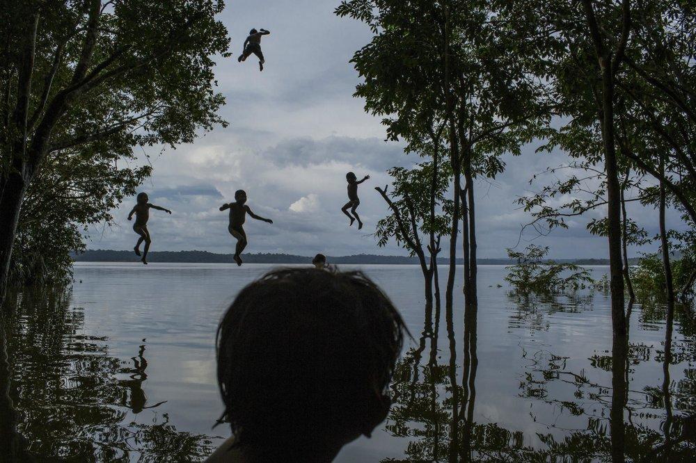 """""""Amazon's Munduruku Tribe""""  Mauricio Lima - Brazil  Segundo lugar en categoría individual  Descripción: Niños juegan en el río de Tapajós , el lugar de la tribu de los Munduruku ubicado en el Amazonas de Brasil. Los Munduruku es una de las etnias más grandes de este país, lamentablemente el gobierno brasileño quiere armar justo por este río una planta hidroeléctrica, por lo que evidentemente ya empezaron a existir conflictos entre los Munduruku y el Gobierno."""