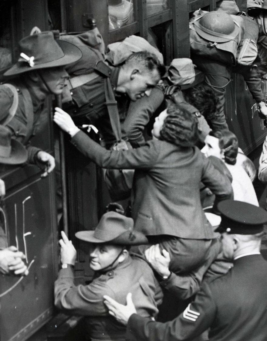 1940 - Unos hombres ayudan a cargar a una mujer para despedirse de su soldado como se debe.