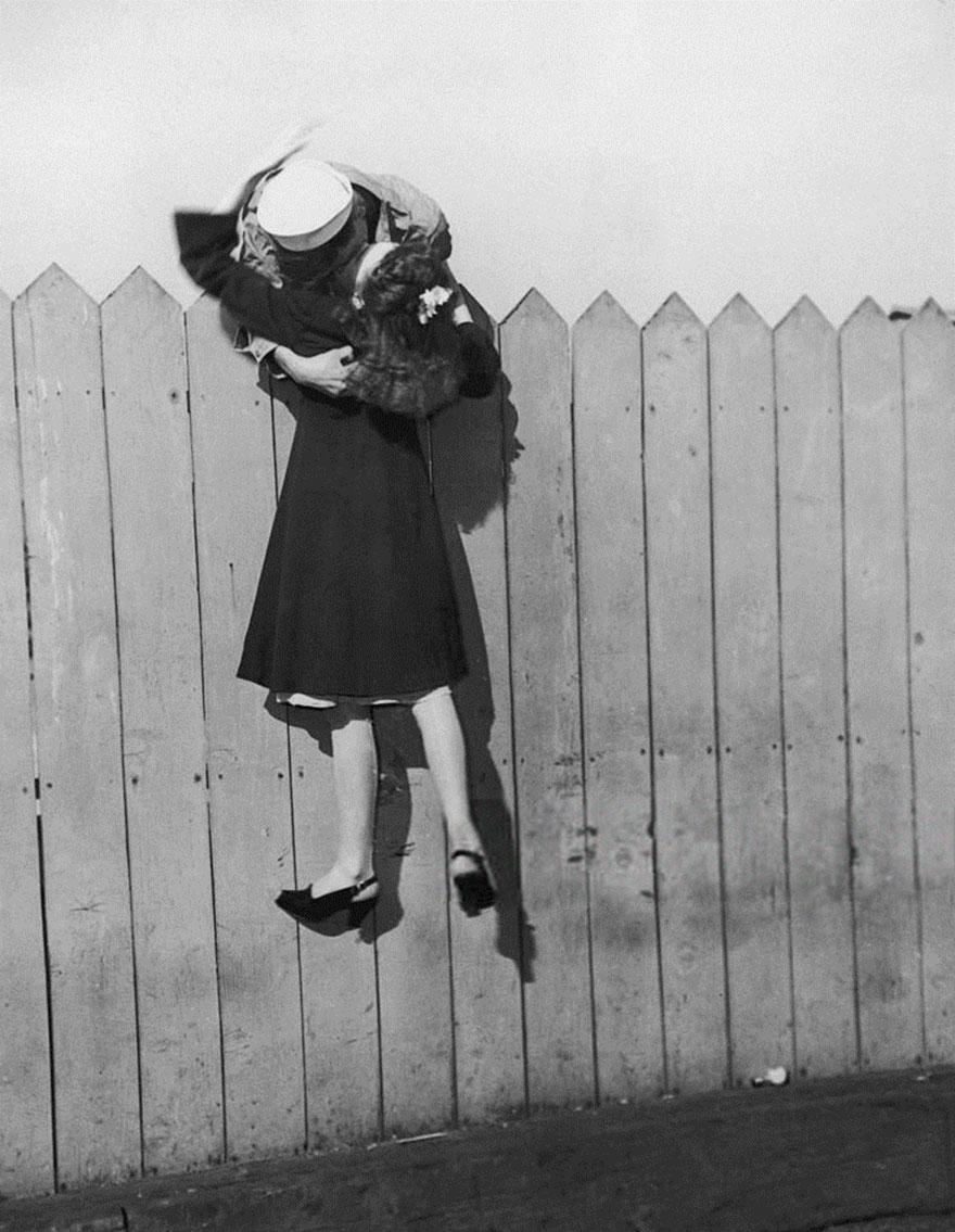1945 - Un hombre se monta a una cerca y carga a su novia para darle un beso.