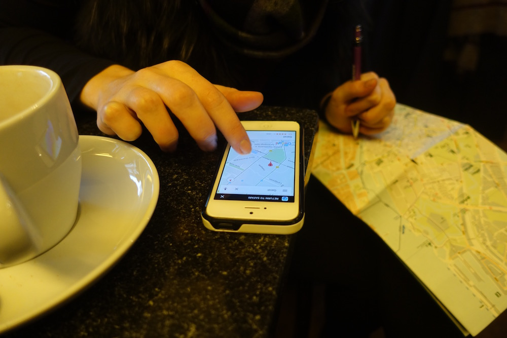 eve writing on a map with an iphone