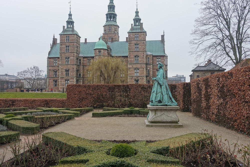 trimmed hedges and statue outside castle rosenborg