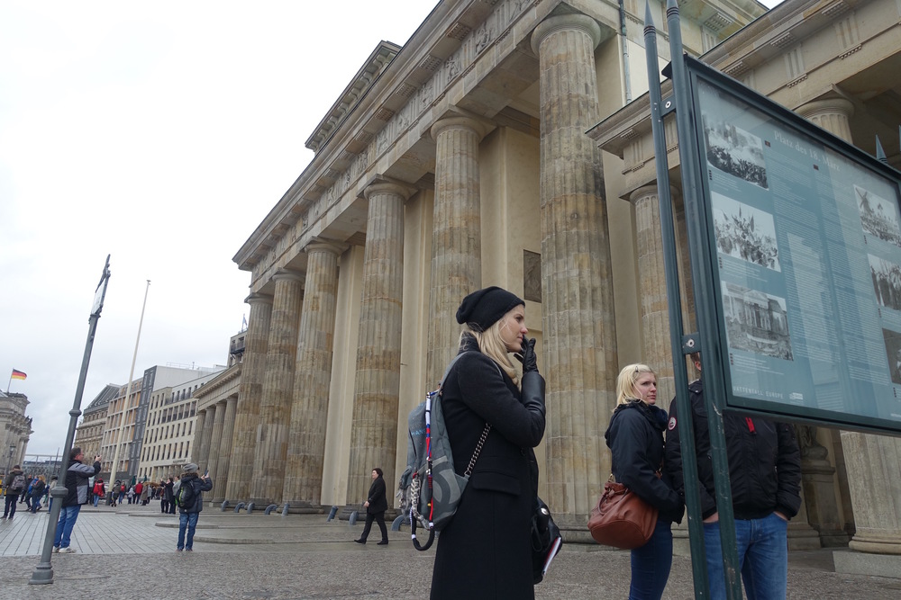 Photo of Eve reading a plaque before the brandenburg gate