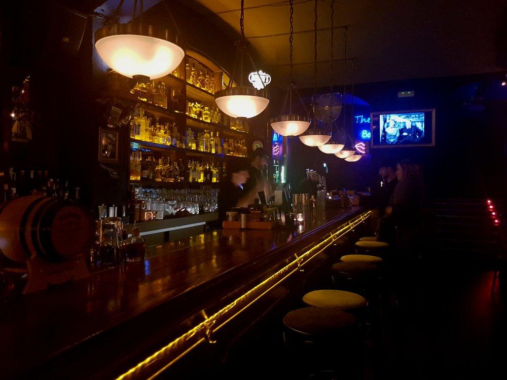 Vista de la barra con barmans mezclando licores de su amplia selección.