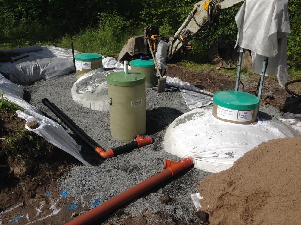 Dräneringsbrunn (mellan tankar) som skall säkerställa att grundvatten aldrig når upp till in/utlopp på tankarna. Brunnen pumpar ev grundvatten till närliggande dike. Nivålarm monterat i pumpbrunn.
