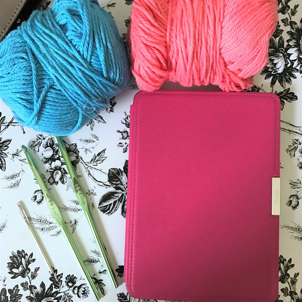 My Kindle Paperwhite, yarn, and a couple crochet hooks.