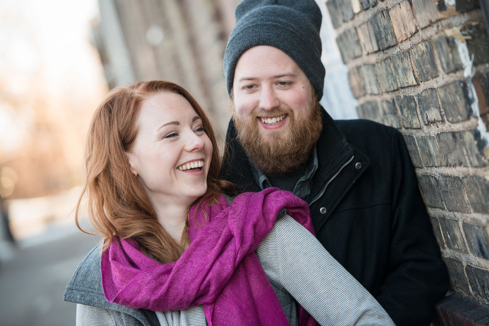 nicole and patrick share a laugh during their Indeed Brewing engagement photo session in Minneapolis