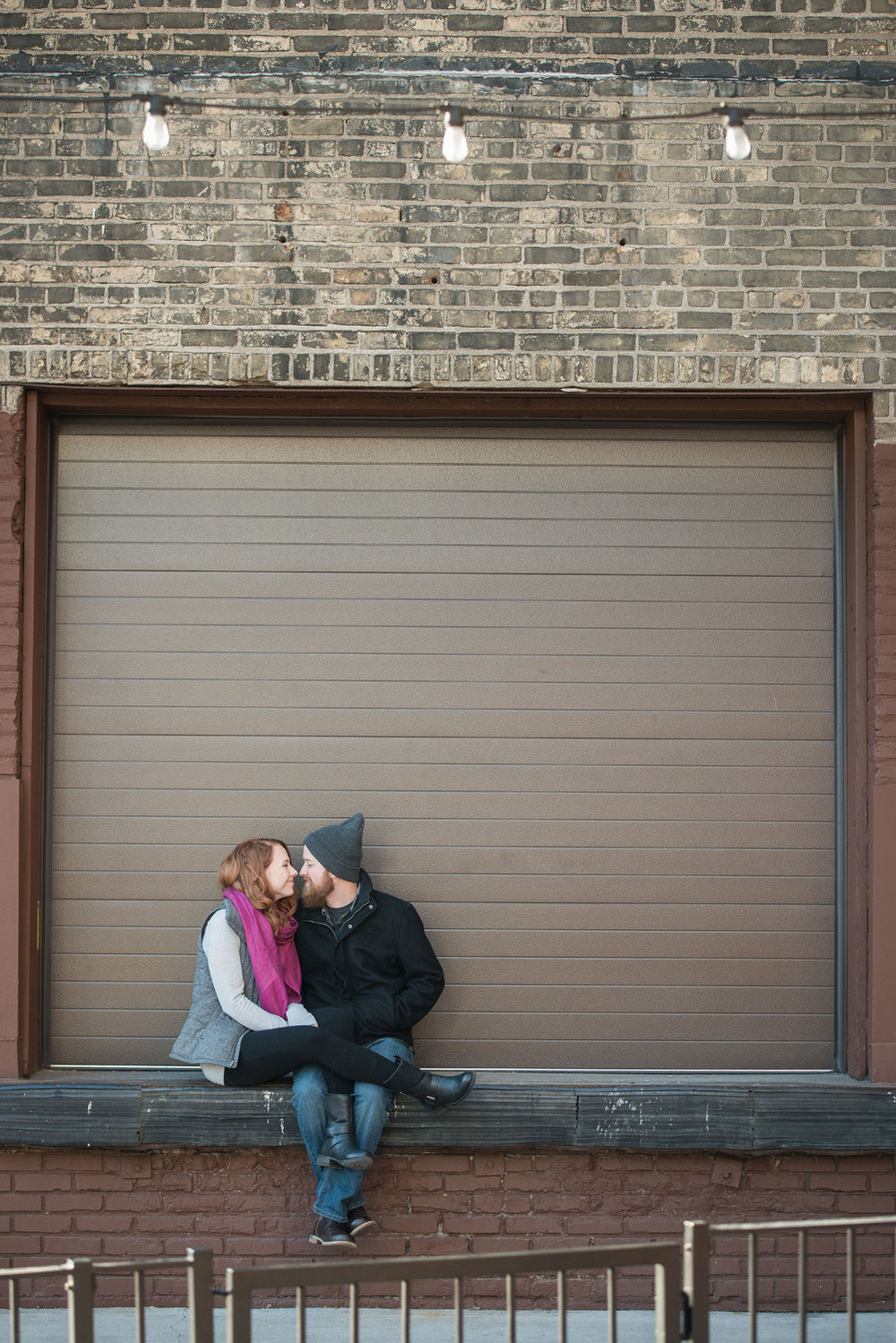 the loading dock at Indeed Brewing Company in Minneapolis served as a bench for this engagement photo session