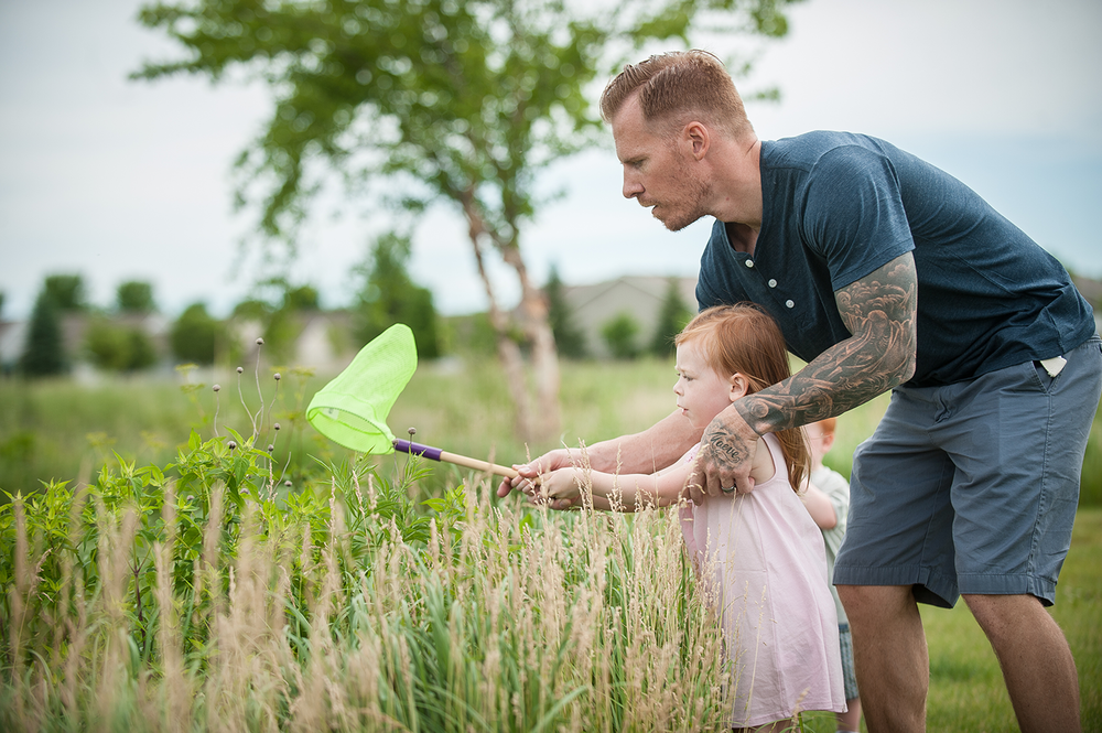 Isla learns to catch dragonflies with the careful guidance of her father during her summer photo session in Northfield, MN
