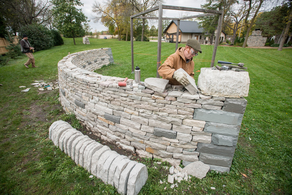 "Daniel Peterson of HabAdapt Landscape Design places a coping stone on an arched, drystone wall that serves as a grounding structure to ""The Cube"" pergola ceremony site at The Gardens of Castle Rock."