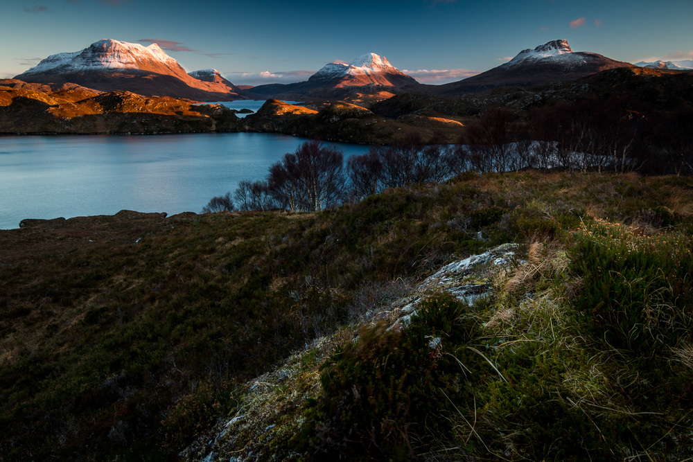 Sunset in Assynt. Looking across Loch Sionasgaig with the peaks of Cùl Mòr, Cùl Beag and Stac Pollaidh on the skyline.