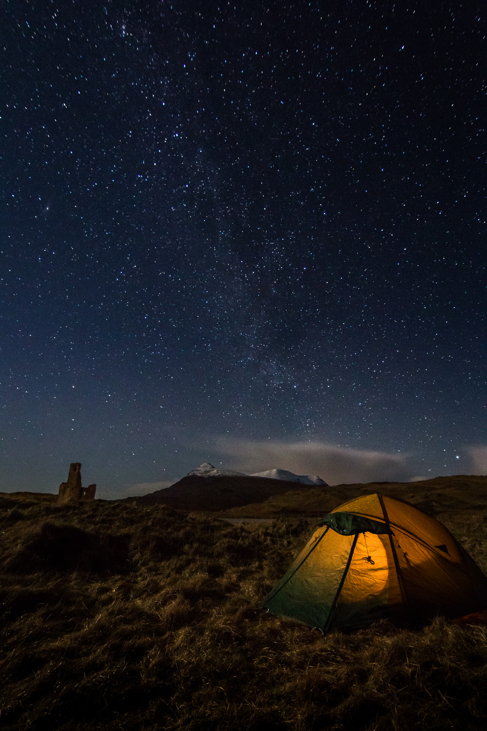 Camp and Ardvreck Castle with the faint tail of the Milky Way overhead.