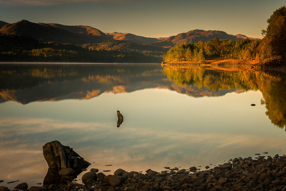 First light on the tree-lined shore of Loch Beinn A' Mheadhoin.