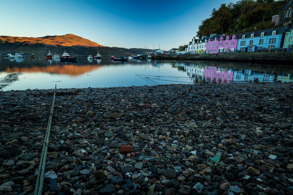 Portree Harbour with the last of the days sun lighting the hill.